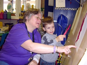 by: Submitted photo, LEARNING MADE FUN — Tigard Playschool teacher Trudy Sang, who will teach a new class for 2-year-olds, works with Collin Parker, 2½, who is the son of Jill Parker, president of the organization.