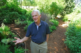 by: Vern Uyetake, Mike Darcy of Lake Oswego stands on a pathway in his garden made of Filbert shells. This portion of his garden is shady and acts as a beautiful transition area between a grassy sunlit garden and a hidden back patio near where wildlife gathers.