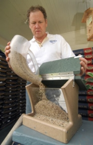 by: Vern Uyetake, Scott Lukens, who started the Backyard Bird Shop stores in the early '90s, holds pieces of the stores' best seller — birdseed.