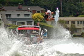by: Ken Borst, Wakerboard professional Rusty Malinoski catches air in front of some of the homes on the bay Sunday.