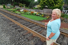 by: Vern Uyetake, Jan Goodwin strolls the railroad tracks near her yard. Five times a day riders on the train can appreciate Goodwin's glowing yard near the shores of Oswego Lake. Goodwin put more than 35 years of expertise into the project, which started her new gardening business called Jewel Box Designs.