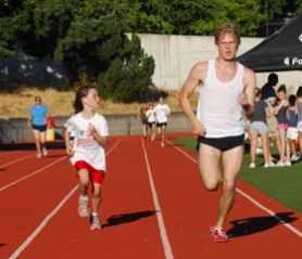 by: Vern Uyetake, Kaylee Nicoll, 8, of Lake Oswego, looks up as Ryan Beaver of Gresham passes her one lap ahead during the predict-a-mile Tuesday night at the Lake Oswego High School all-comers track meet.