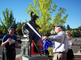 "by: Submitted photo, At Sunday's Gallery Without Walls celebration Robert Hess cuts the ribbon off his ""Drummer with Rooster"" sculpture."