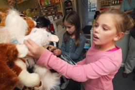 by: Vern Uyetake, Samantha Zito takes a Webkinz toy off the shelf at West Linn's Lavender Bleu store.