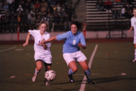 by: Vern Uyetake, Lakeridge's Casey Costello, right, looks to dribble around a Lake Oswego defender during last Thursday's Civil War game. Costello scored an early goal but Lake Oswego was able to earn a 1-1 tie.