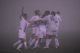 by: Vern Uyetake, Members of the Lakeridge boys soccer team celebrate after scoring a goal during Tuesday's playoff against Roseburg. The Pacers overcame a thick layer of fog to win the game 2-0.