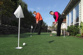 by: Vern Uyetake, Rain or shine, Bonnie Freiston,left, and Donna Lindell can practice their putting strokes in the backyard of their Lake Oswego home. It's now a good place for golfers and dogs.