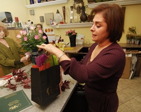 by: Vern Uyetake, Maryam Bazagran, owner of Artistic Flowers in the Lake Grove neighborhood, shows off some of her popular, seasonal arraingements.