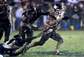 by: Vern Uyetake, Lake Oswego's Zach Young eludes Canby tacklers enroute to 161 yards rushing in the mud and three touchdowns.