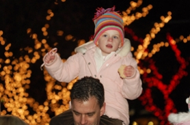 by: Vern Uyetake, Natalie Fagen enjoys a cookie, candy cane and the view  from the shoulders of her dad Jeff Fagen during Friday's tree lighting event at Millenium Plaza Park.