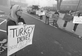 by: Vern Uyetake, Students accepting donations of frozen turkeys Wednesday included senior Rachelle Svaren, left, at Lake Oswego High School, along with other sign holders.