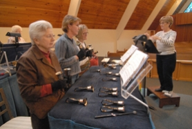 by: Vern Uyetake, Linda Woods directs a rehearsal of the hand bell choir of the Lake Oswego United Methodist Church. Not even a broken foot has stopped Woods from getting ready for Sunday's big Christmas concert.