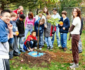 by: David F. Ashton, Katherine Drotos (far right) helps kids learn about some of the trees planted at the Learning Garden.