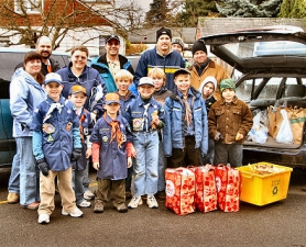 "by: David F. Ashton, While ""Scouting for Food"" on Saturday, December 1st, this year, the Cub Scouts of Pack 64 braved sleet and snow while gathering hundreds of pound of food for the Oregon Food Bank."