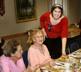 by: David F. Ashton, Job's Daughter Kelsey Richert serves an early Thanksgiving dinner to guest Beryl Parker.