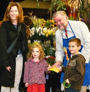 by: David F. Ashton, Portland Mayor Tom Potter, at New Seasons Market on November 19th, pitches a Sellwood family – Teri, Sam and Sofia Laos – about helping Loaves & Fishes Centers.