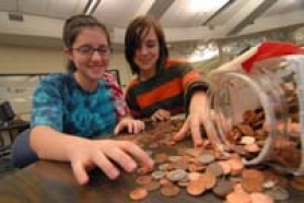 by: Vern Uyetake, Lakeridge High School students, from left, Erin Young and Shelley Marsee sort a jar of change they collected from students and staff at their school. The girls have $800 to go in order to build a school in Kenya through the non-profit organization Koins for Kenya, based in Utah.