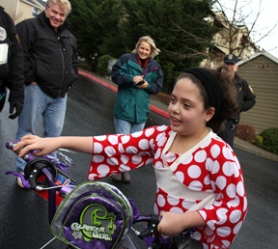by: Jaime Valdez, BIKE BONANZA — At one of the stops during Saturday's great bike giveaway, Jessica, 8, wheels away her new bike while (from left) Bob Brown, Desiree Brown and Chief Bill Dickinson look on.