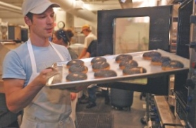 by: SARAH TOOR, In the basement kitchen of Kenny & Zuke's Delicatessen, head baker Tim Healea pulls a batch of poppy seed bagels out of the oven.