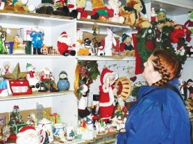 by: Gini Bramlett, Vernonia resident Tori Fallau looks over the selection of Christmas ornaments and decorations at the Christmas store set up by Goodwill Industries in an old gas station in the middle of town. Fallau, her husband and her two children are living in the family room of a friend's home until flood damage to their townhouse is repaired.