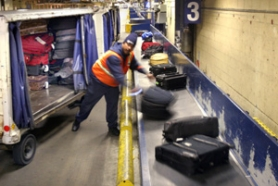 by: JIM CLARK, One of about 10,000 people who work at PDX, this baggage handler unloads freshly landed suitcases on a belt for passenger pickup.
