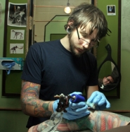 by: KATIE HARTLEY, Ryan Mason inks a tattoo featuring vegetables on client Jeffrey Wilson's arm. No animal products are used at the business, Scapegoat Tattoo.