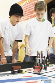 by: Tommy Whitcomb, Aaron Streblow and Tayler Young (above) operate their team's Lego robot.