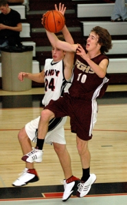 by: Zack Palmer, Forest Grove senior Dusty Klein gets fouled by Sandy's Jason Summerfield while attempting a layup during last Wednesdaay's non-conference basketball game.