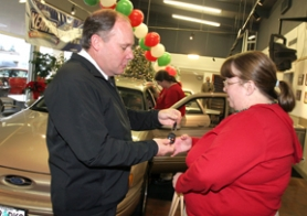 by: Jaime Valdez, GIFT ON WHEELS — Beaverton Ford Manager Tym Barker hands over the keys of a Ford Taurus to Debbie, a former foster care provider.