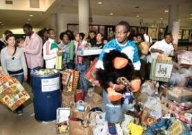 by: Carole Archer, In the foreground, Isaiha Huff, 17, a senior at Reynolds High School and a member of the Unity Club, helps organize toys that were donated to a Christmas drive for families at the school. The drive is among the service projects the club undertakes.
