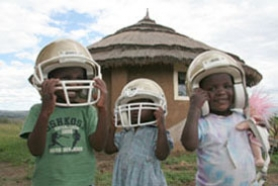 by: SUBMITTED PHOTO, Orphans at the Mission in Action Orphanage located on the outskirts of Nakuru, Kenya, try out Lakeridge High School football helmets that are being used by night guards at the facility for protection against thieves. There is no indication that the ethnic violence that has killed more than 300 people in Kenya since last Thursday's disputed presidential election has affected life at the orphanage.