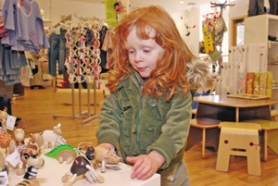 by: KATIE HARTLEY, Many trendy stores are offering goods for the littlest consumers. Here, Bridget Marsh tries out some wooden animals at Little Urbanites in Northwest Portland. The co-owner of another baby boutique, Milagros, says parents' purchases don't have to come with a big price tag in terms of either dollars or ethics.