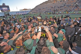by: ©2008 Brian Kanof, The trophy was passed around and water buckets were emptied in the celebration after the University of Oregon's Sun Bowl victory Monday over South Florida.