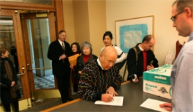 by: L.E. BASKOW,  Portland businessman Sho Dozono (center) officially registers within the City Hall auditor's office for his bid at being the next mayor of Portland. City Elections Officer Andrew Carlstrom (right) awaits the form for processing as the Dozono family and friends are there for support.
