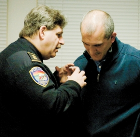by: Chase Allgood, Cornelius Police Chief Paul Rubenstein bends the ear of state Sen. Bruce Starr at the Jan. 3 forum on the Connell House, a secure residential facility for the criminally insane that recently opened in Cornelius.