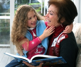 by: Jaime Valdez, SHARING A LAUGH — While reading a story, Suzie Duncan-Winn shares a laugh with her mom Bonnie Duncan, who with her husband Michael Winn works with the 7-year-old autistic child on expressing emotions