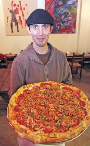 by: KATIE HARTLEY,  Ryan Wade, of Good Neighbor Pizzeria, holds an Old World pizza topped with salami, peppers, olives, onions and pepperoni.