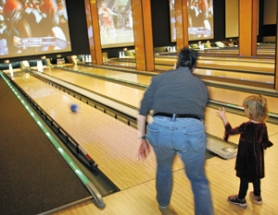 by: KATIE HARTLEY, Ann Marie Chinn teaches daughter Halle Chinn-Raicht the ways of the lanes at Southeast Portland's newly refurbished Grand Central Restaurant and Bowling Lounge.