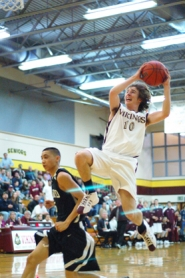 by: Kathy Storm, Forest Grove senior Dusty Klein goes airborne for a shot last Friday night in a game against Tigard.