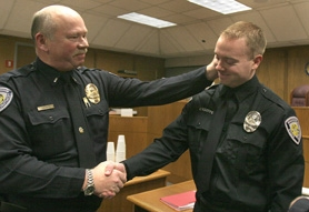 by: Jaime Valdez, Police Lt. Kevin O'Keeffe congratulates his son John after pinning his Beaverton police shield on him during Monday's swearing-in reception.