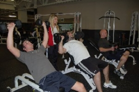 by: Jessica Gregg, Fitness consultant Kelly Kero chats with Sandy residents Cody Giusto, left, and Jeff Flood during a workout at Mt. Hood Athletic Club. Lifting weights isn't as important, though, as just making a habit of going to the gym.