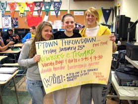 by: Barbara Sherman, TOUTING THE THS TIGERS — Tigard High School senior Caitlyn Bese (left), junior Corinn Waltrip and senior Sarah Rehm, all sports marketing II students, hold up a poster they made to promote the Jan. 25 double-header against Newberg High School.
