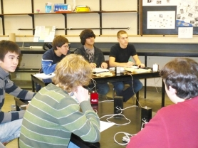 by: Gini Bramlett, Facing from left to right are Scappoose High School students Angus Toland, Johnny Dutra and Jared Graham. In the foreground are (left to right) Joe Anderson and James Rogers. The five seniors have practice sessions after school to learn how to respond to science and math questions using electronic beepers that are similar to those at the science bowl competition on Feb. 2 at Portland State University.