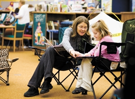 by: Chase Allgood, Echo Shaw teacher Wendy Seitz listens to Hanna Knotts read during Camp Read-A-Lot.