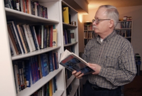 by: Vern Uyetake, Keith Rowell, left, chooses from a vast library of UFO-related literature at his West Linn home.