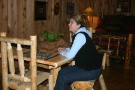by: Jessica Gregg, Karen Liebelt admires the new, cabin-like hand-made furniture showroom at her and her husband's store, Douglas Ridge. People ask if they can rent it for the weekend, she says.
