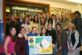 by: Garth Guibord, Leadership students hold a poster they made that shares the story of the African boy they sponsored.