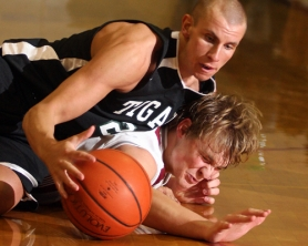 by: JAIME VALDEZ, FLOOR BURNS — Tigard High School junior Matt Alexander (top) and Tualatin junior Brandon Troxel battle for a loose ball.