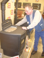 by: Cliff Newell, Chuck Blaisdell, hearth manager of Coastal Farm & Ranch demonstrates how to operate a pellet stove. The stoves work off fuel from tiny wood pellets, shown at left.
