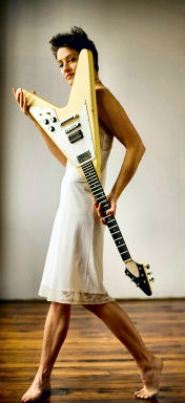 by: Carl Evans, Lounge singer Jennifer Faust strikes a pose with her white guitar in this promotional photo by fashion photographer Carl Evans.